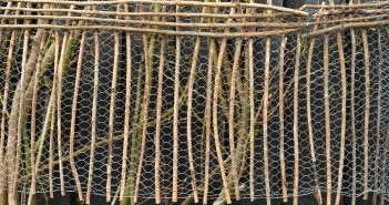 Flettet hegn af hønsetråd og grene