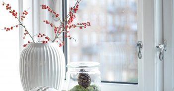 Juledekoration med røde bær, mos og kogler